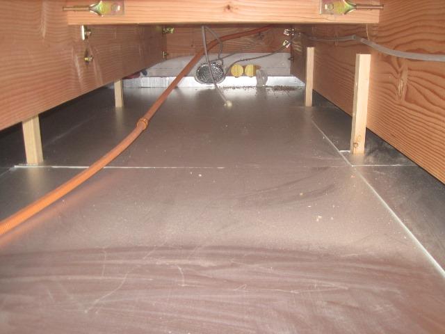 二階床下空間、奥に見える楕円形のダクトは送風ファンに繋がっています。